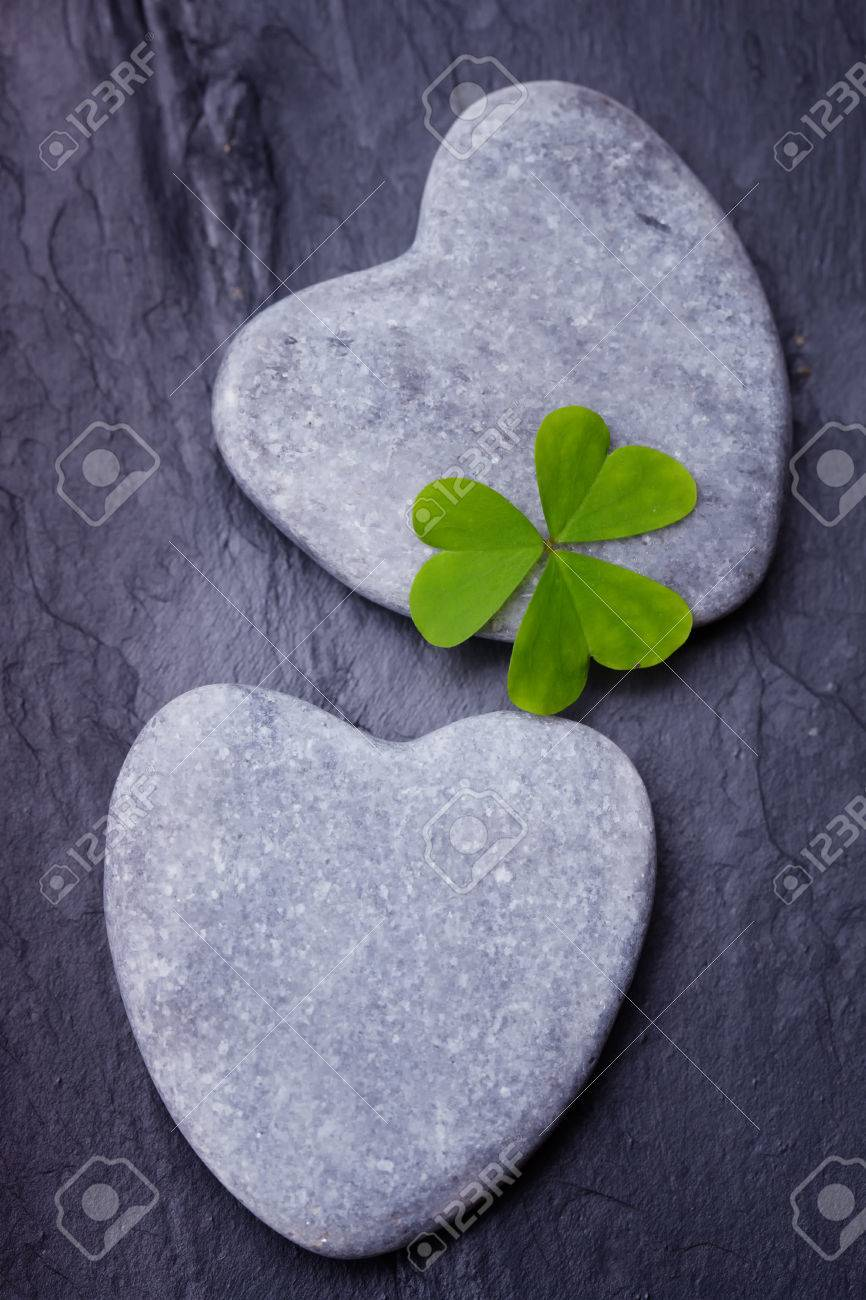Two Grey Heart Shaped Rocks With Three Leafed Clover On A Tile ...