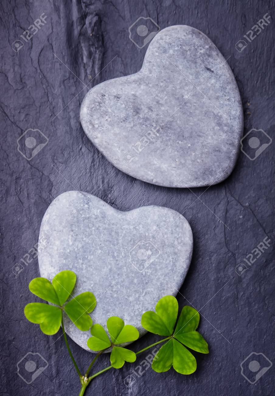 Two Grey Heart Shaped Rocks With Three Lucky Clovers On Tile.. Stock ...