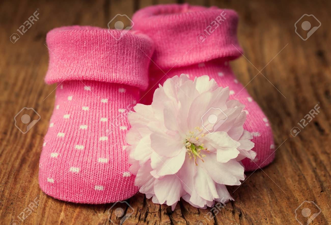 Baby Girl Shoes With Pink Flower On Vintage Wooden Surface Stock