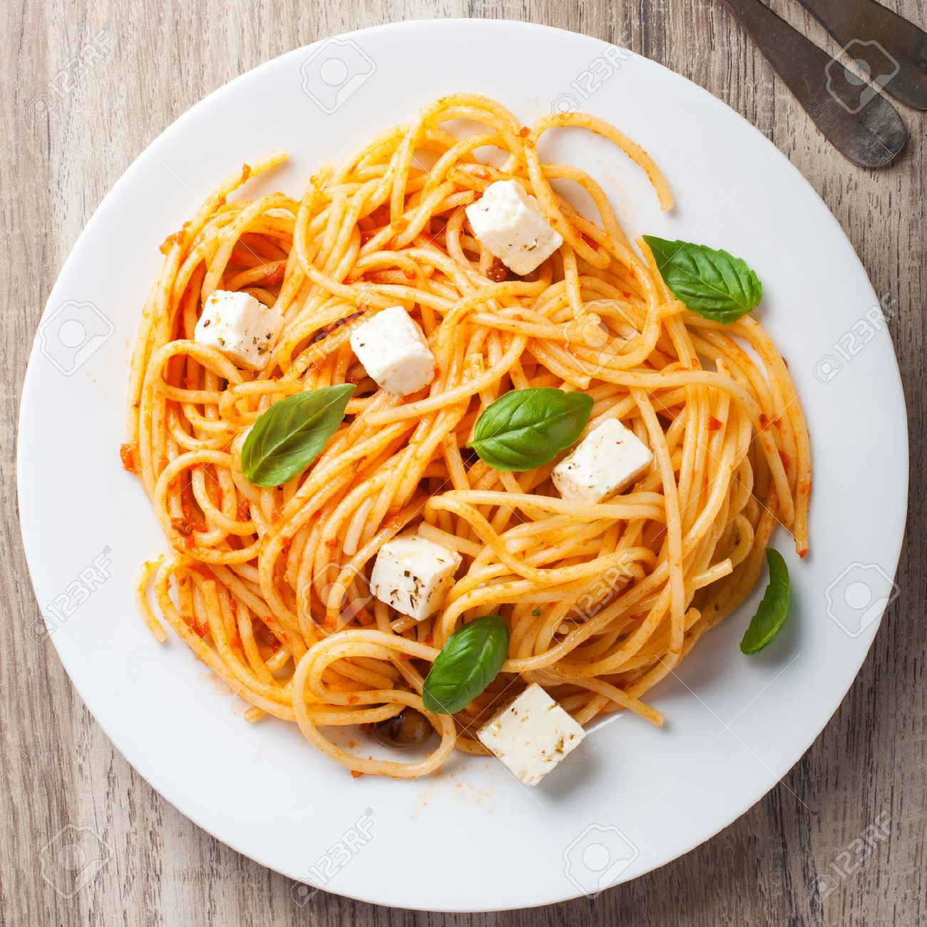 Spaghetti With Tomato Sauce Feta Cheese And Basil Leaves On White Plate Wooden Background