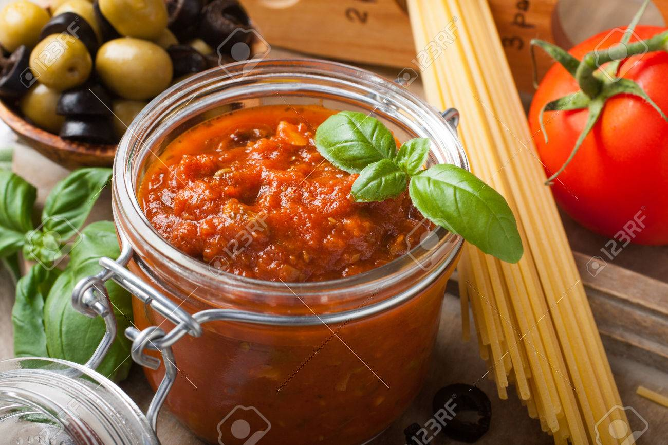 Glass jar with homemade classic spicy tomato pasta or pizza sauce with olives and basil. Italian healthy food background. - 43207263