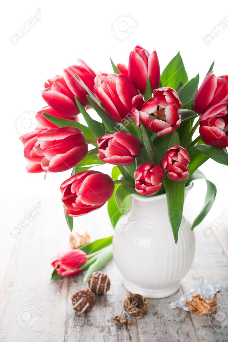 Bouquet Of Pink Tulips In Vase And Chocolate Candies On The White