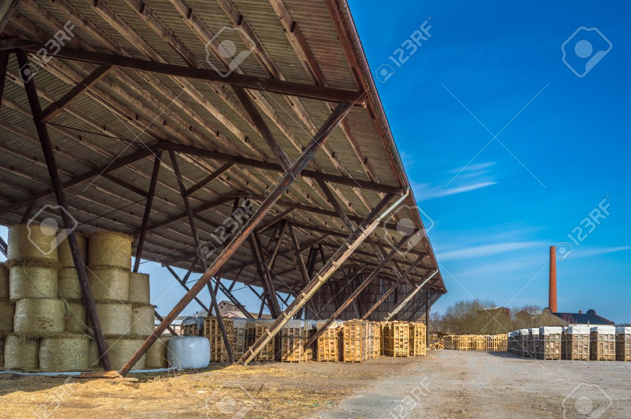 Long roof protecting straw bales and fire wood  To the right