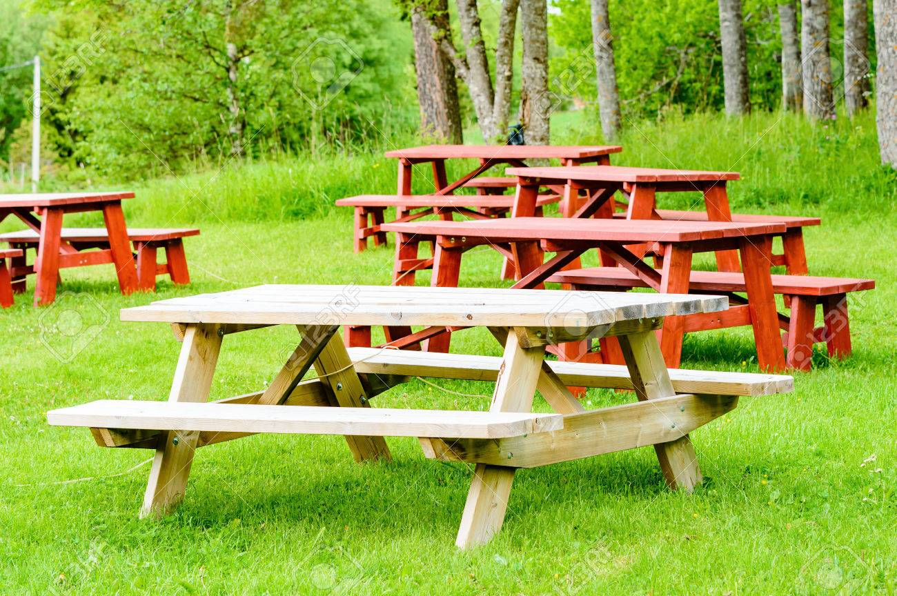 Garden Furniture On Grass red and unpainted garden furniture on green grass with forest
