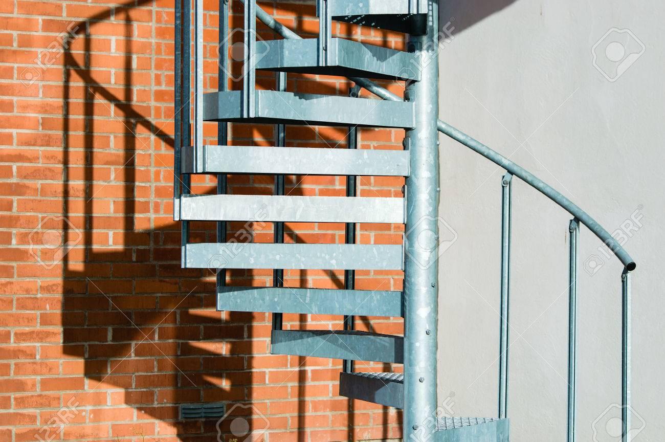 foto de archivo escaleras de caracol de aluminio en el exterior de un edificio su sombra se ve en la pared de ladrillo detrs