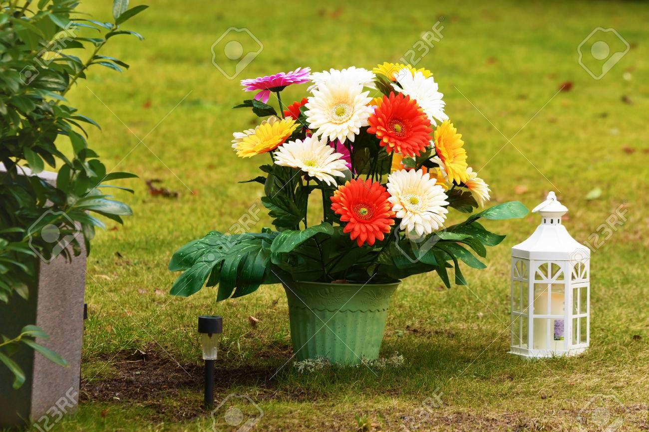 Fleur En Plastique Colore Dans Un Pot A Cote D Une Pierre Tombale