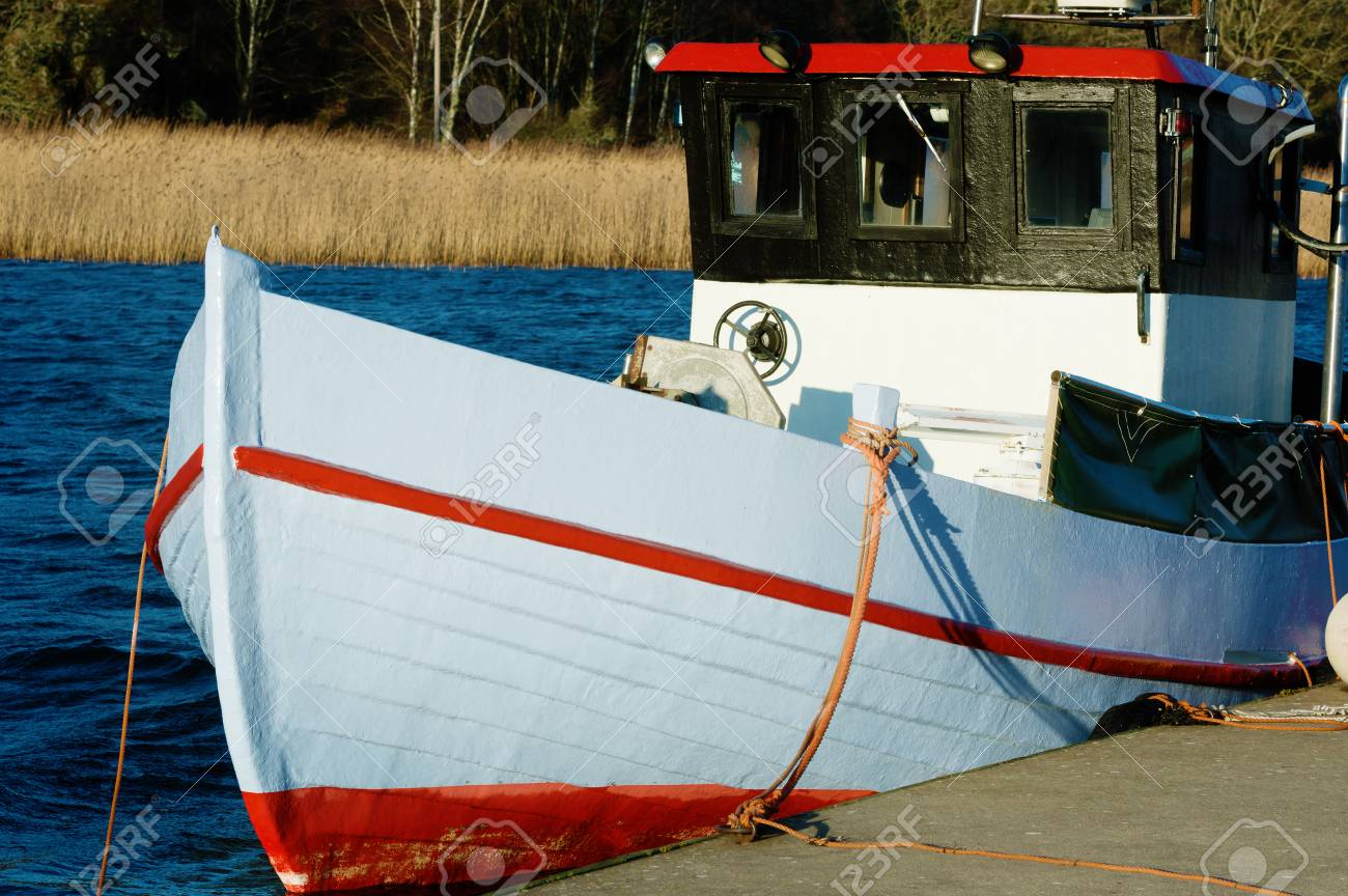 A small red and white fishing boat moored at dockside with sea