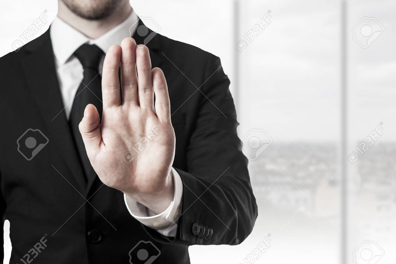 businessman in black suit holding hand stop in office room - 30031871
