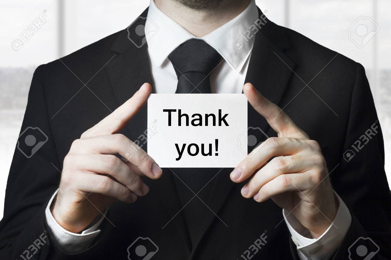 businessman in black suit holding small white card thank you - 30485531