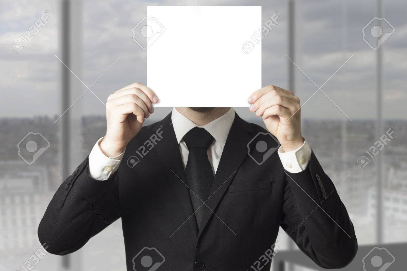 businessman in black suit hiding his face behind paper sign - 30730032