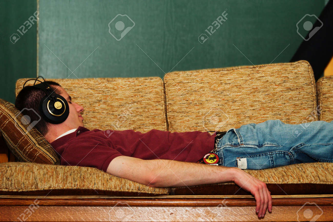 A Guy Lying On A Couch Listening To Music. Stock Photo, Picture ...
