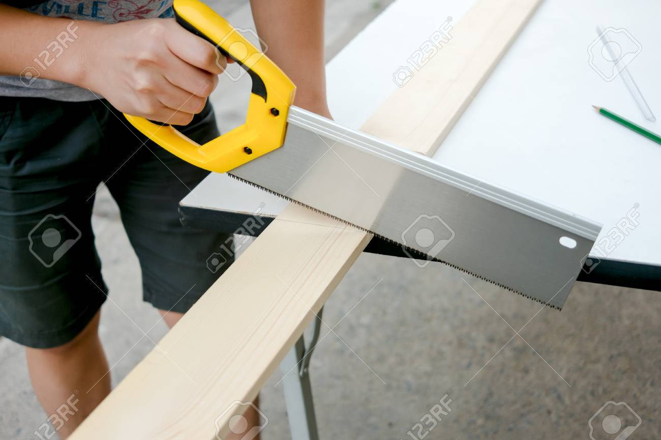 Carpenter Working On A Hand Saw Cutting Wood Board Stock Photo