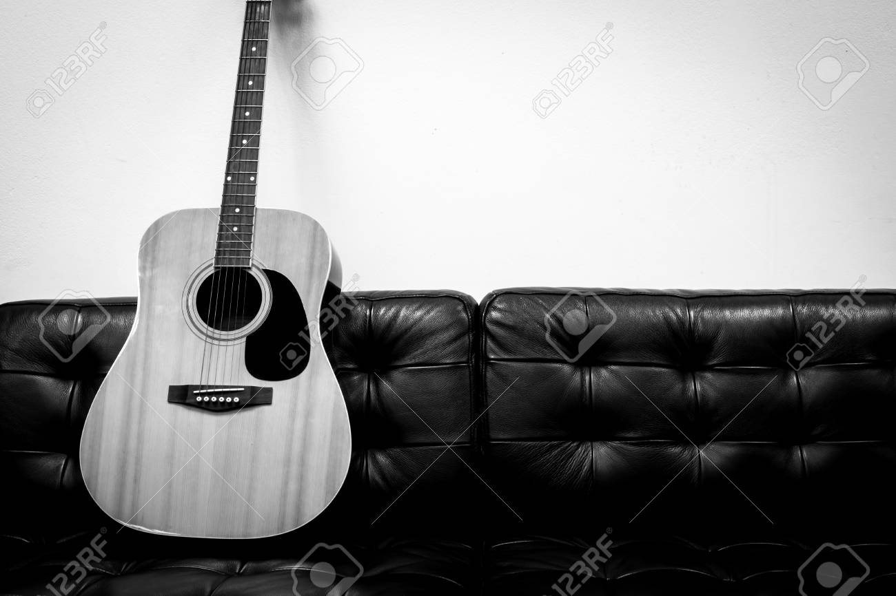 Acoustic guitar on the sofa black and white color stock photo 69858888