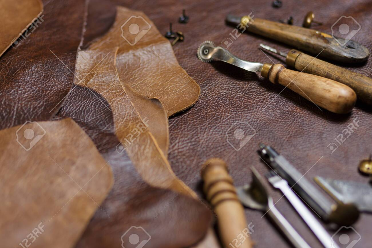 Leather craftman's work desk. Pieces of leather and working tools on a working table - 139530776