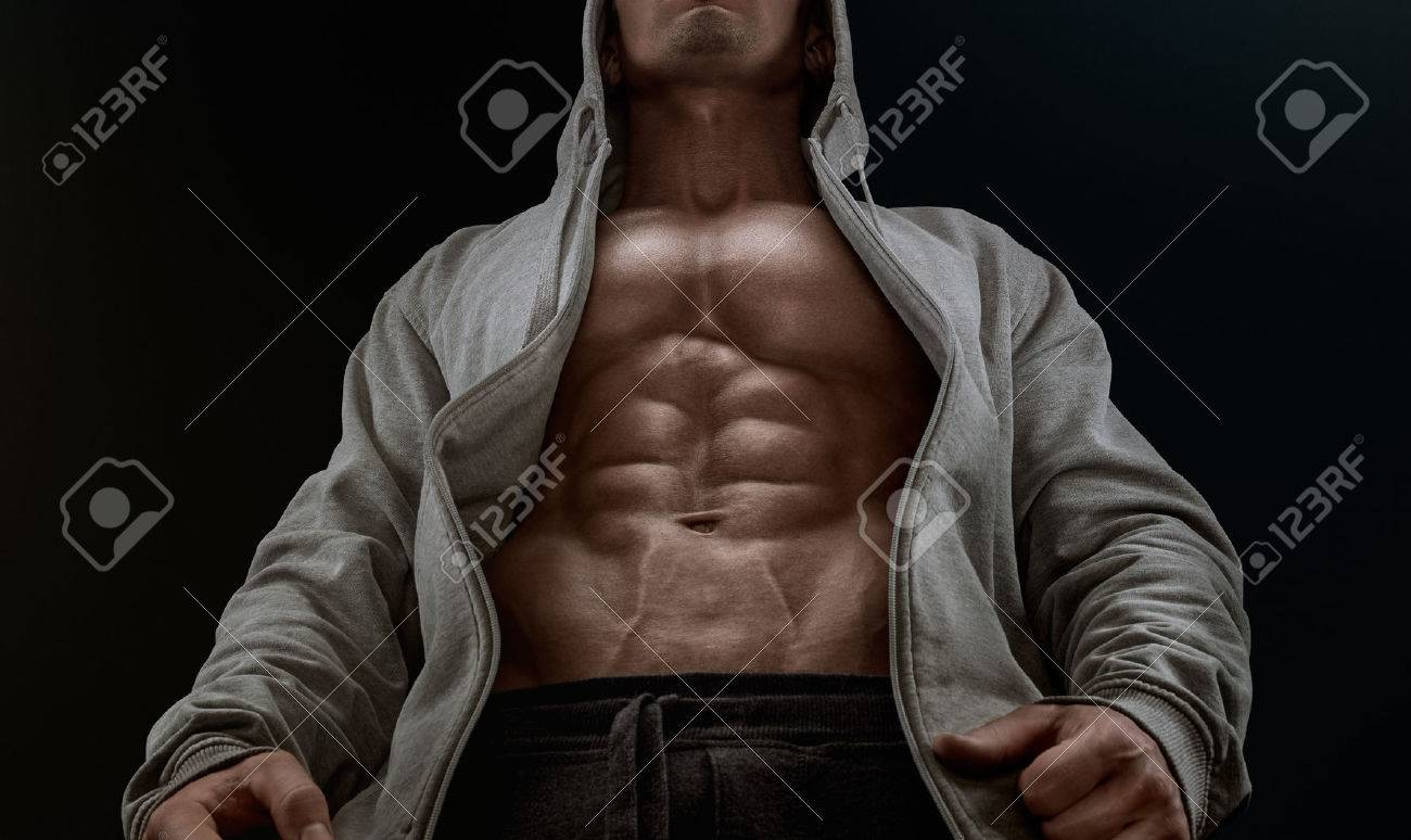 Bottom view of young strong bodybuilder showing off his physique against black background. Confident young fitness man with strong hands abs and abdominal muscles. Dramatic light. Standard-Bild - 41379851