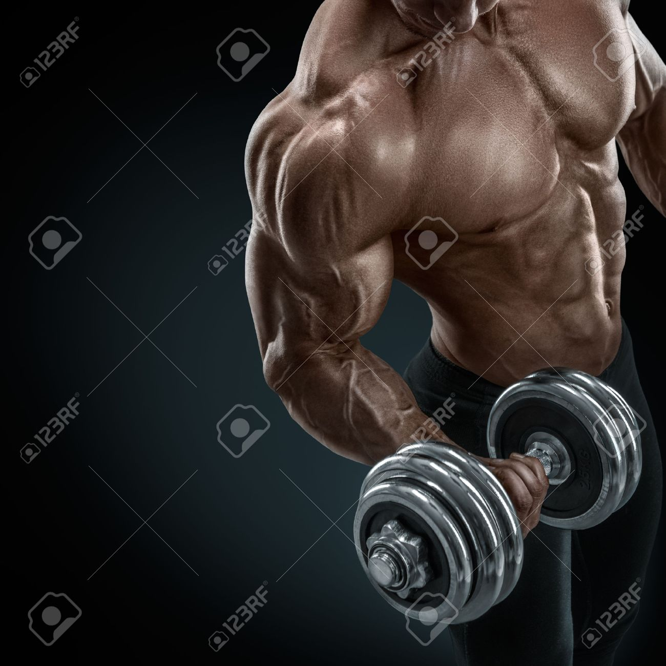 Closeup of a handsome power athletic guy male bodybuilder doing exercises with dumbbell. Fitness muscular body on dark background. Standard-Bild - 41379856