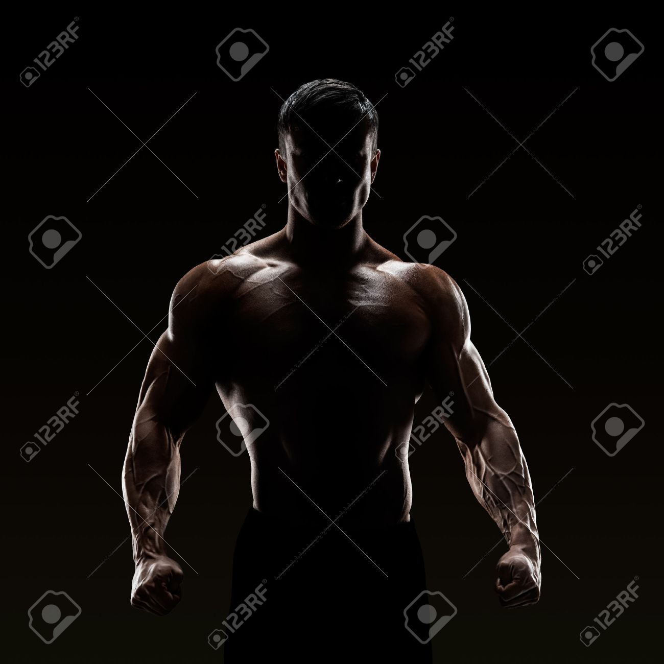 Silhouette of a strong fighter. Confident young fitness man with strong hands and clenched fists. Standard-Bild - 41379859