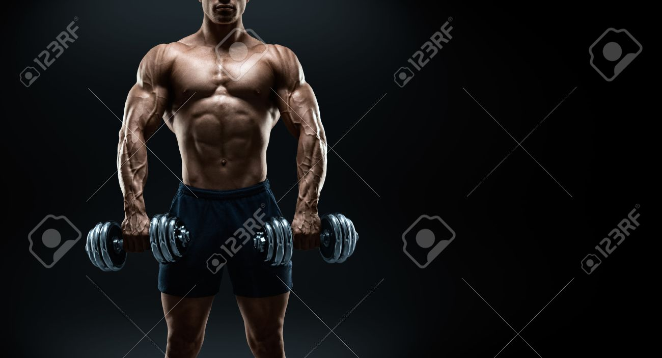 Handsome power athletic man bodybuilder doing exercises with dumbbell. Fitness muscular body on dark background. Black and white photo with copy space Standard-Bild - 41379861