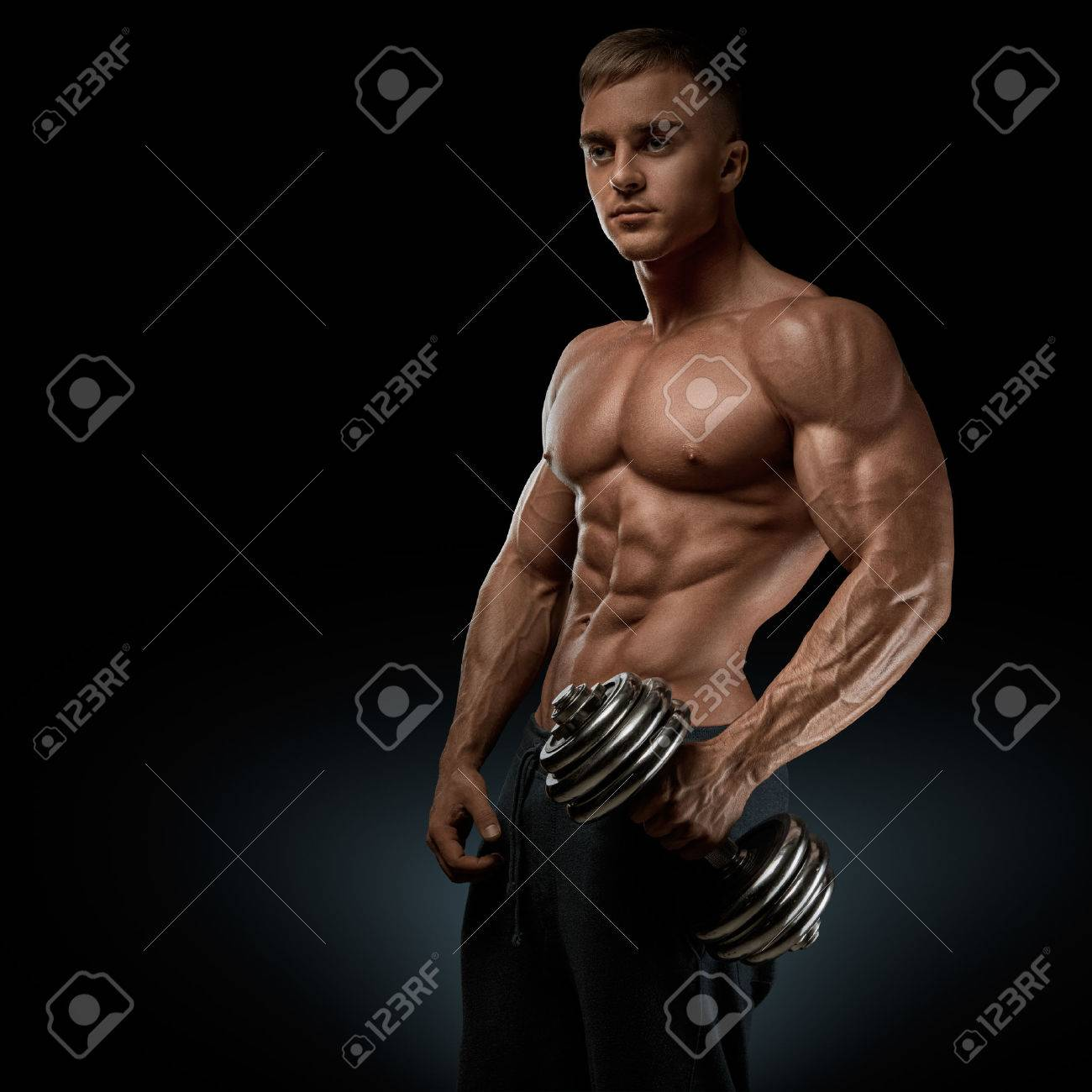 Handsome power athletic man with dumbbell confidently looking forward. Strong bodybuilder with six pack perfect abs shoulders biceps triceps and chest Standard-Bild - 41421924