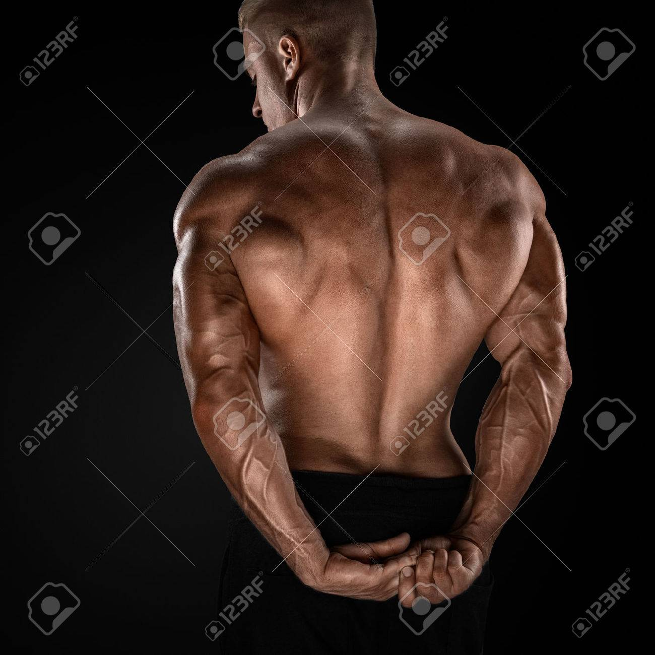 Handsome power athletic man showing his back. Strong bodybuilder with shoulders biceps triceps and chest Standard-Bild - 41421933