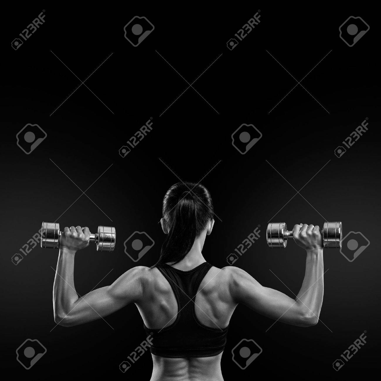 Fitness sporty woman in training pumping up muscles of the back and hands with dumbbells. Black and white concept image Standard-Bild - 41422117