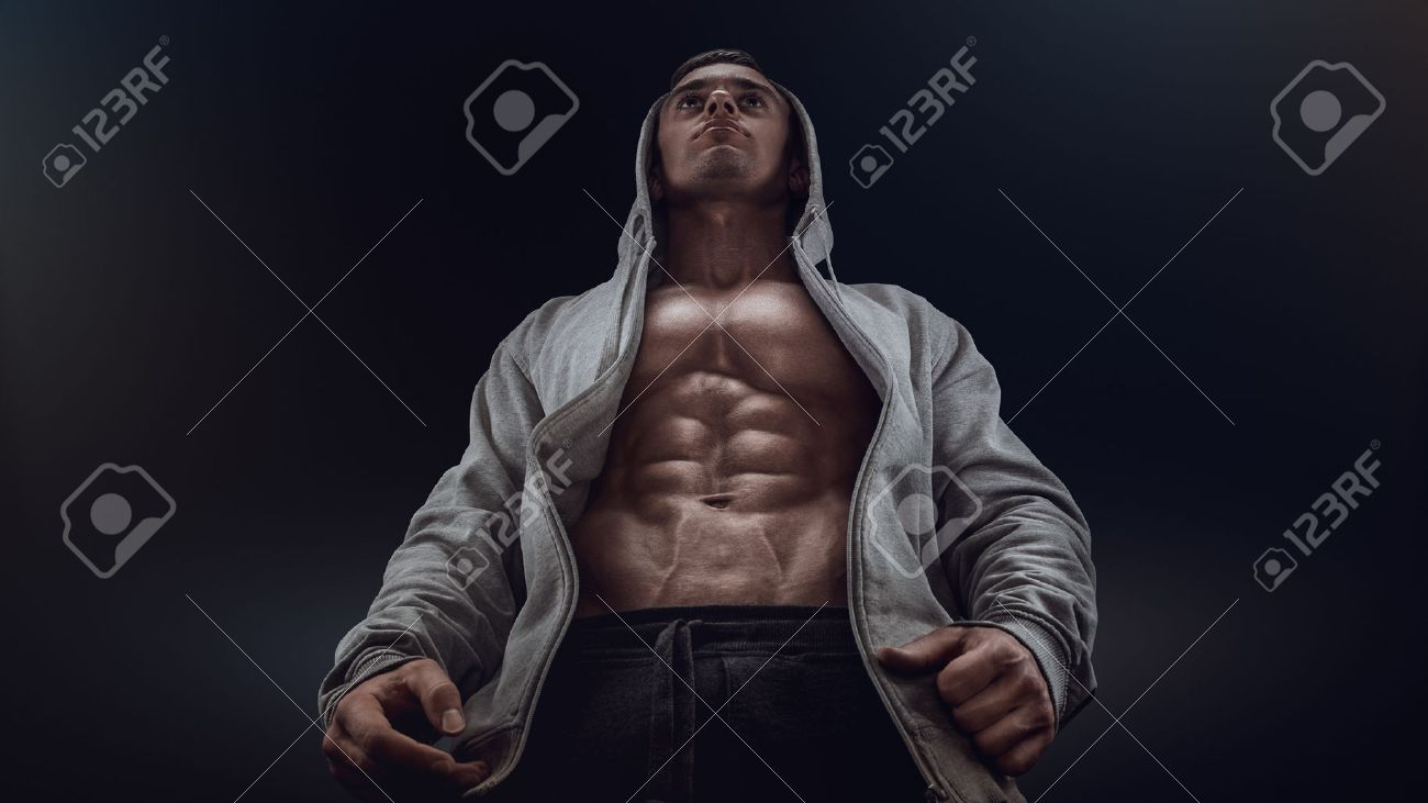 Bottom view of young strong bodybuilder showing off his physique against black background. Confident young fitness man with strong hands abs and abdominal muscles. Dramatic light. Standard-Bild - 41422253