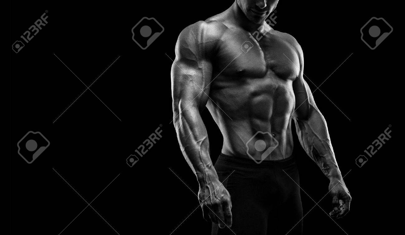 Muscular and fit young bodybuilder fitness male model posing over black background. Black and white photo with copy space Standard-Bild - 41423187