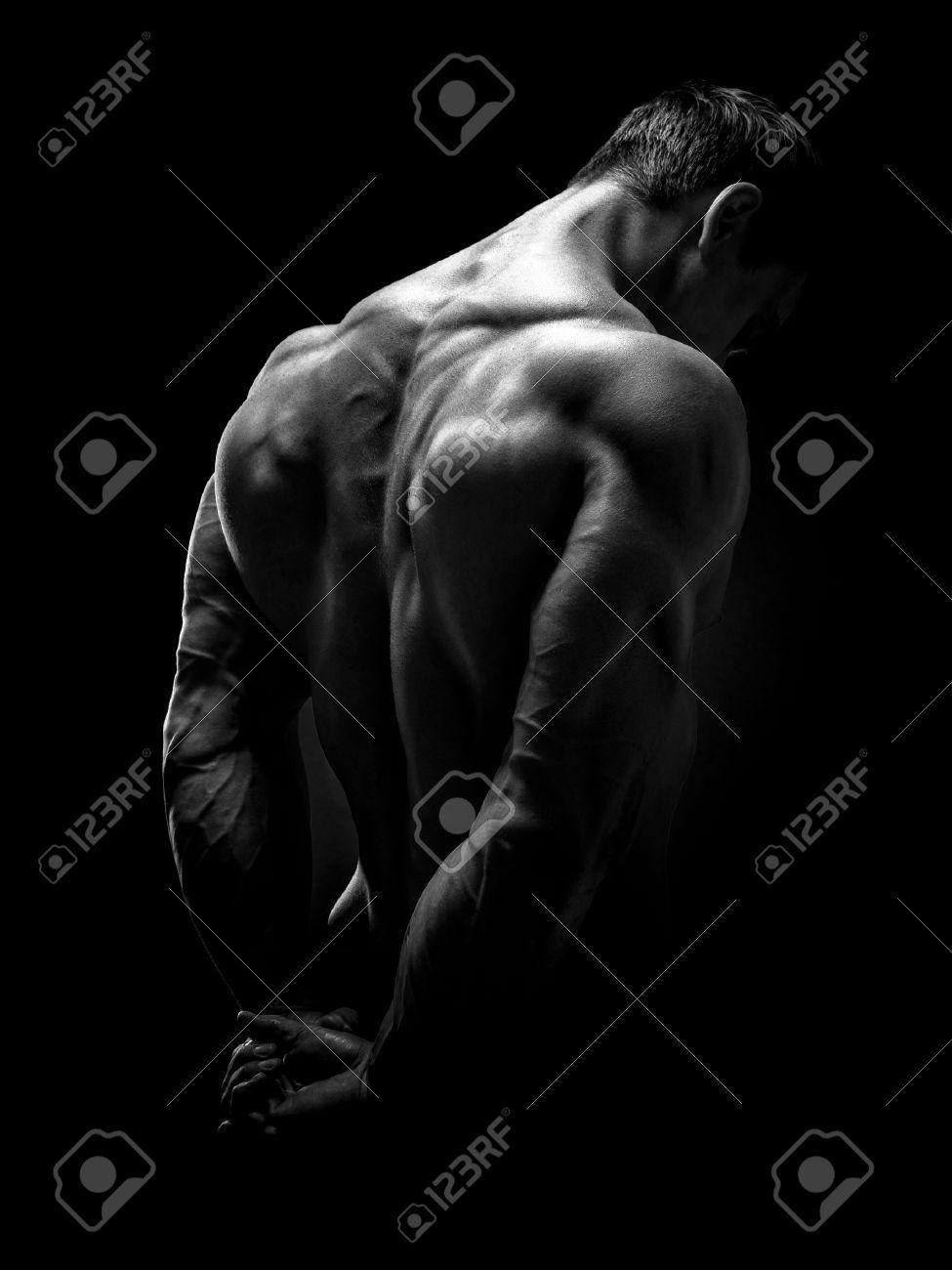 Handsome muscular male model bodybuilder preparing for fitness training turned back. Studio shot on black background. Black and white photo. Standard-Bild - 41423194