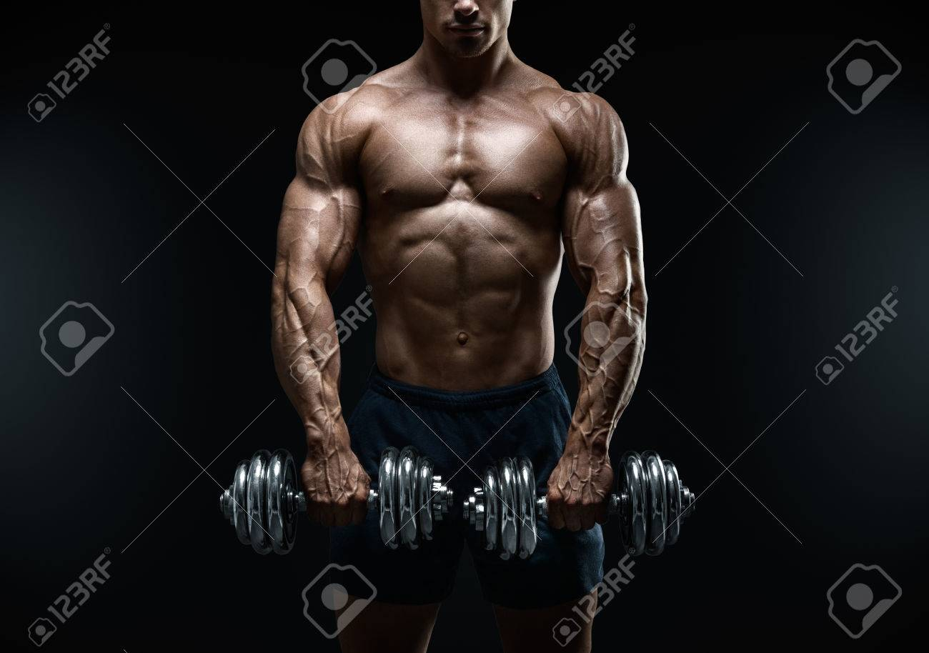 Handsome power athletic guy bodybuilder doing exercises with dumbbell. Fitness muscular body on dark background. Standard-Bild - 41423206
