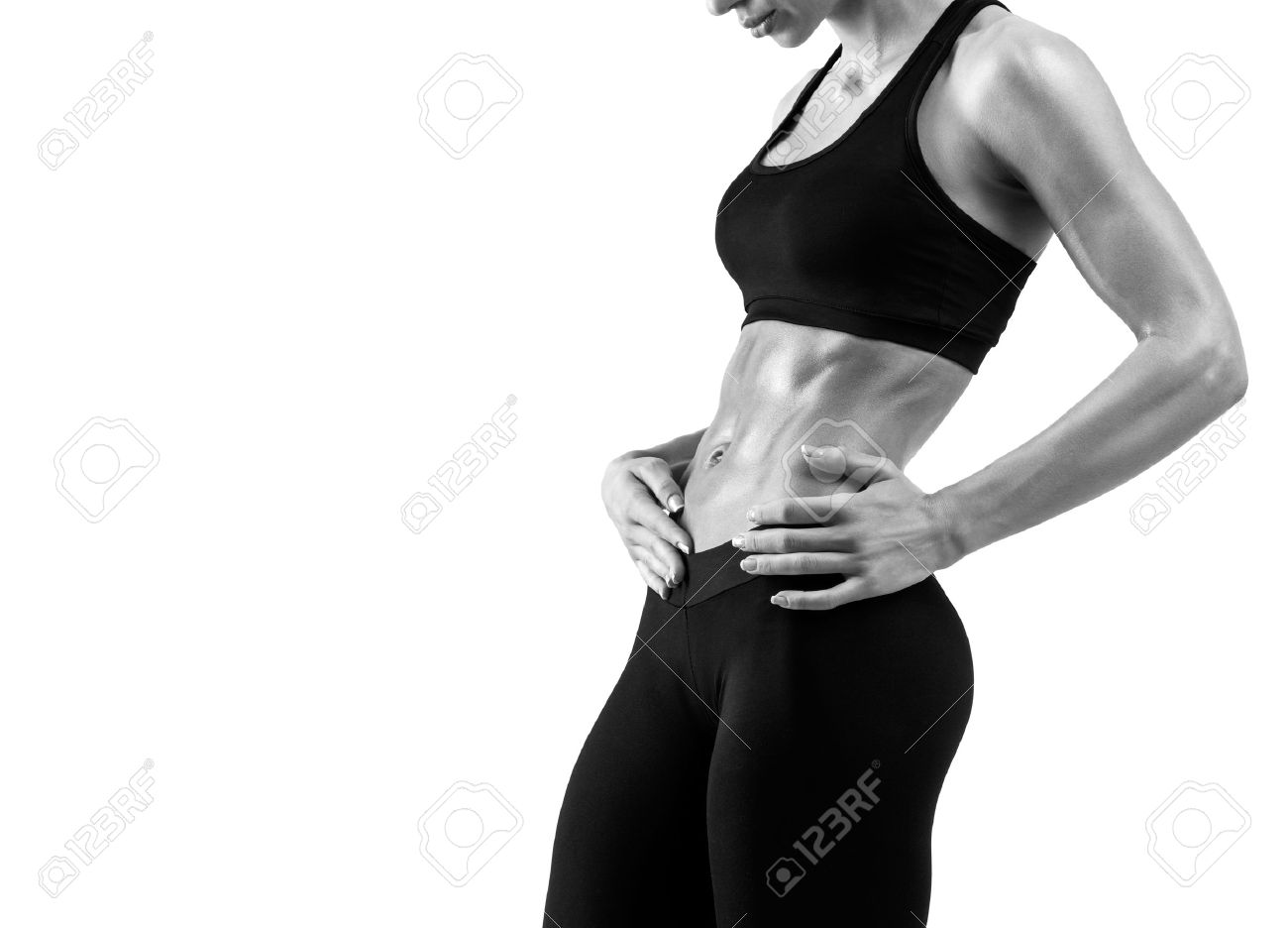 Fitness sporty woman showing her well trained body isolated on white background. Strong abs showing. Black and white photo with copyspace for text. Standard-Bild - 41423854