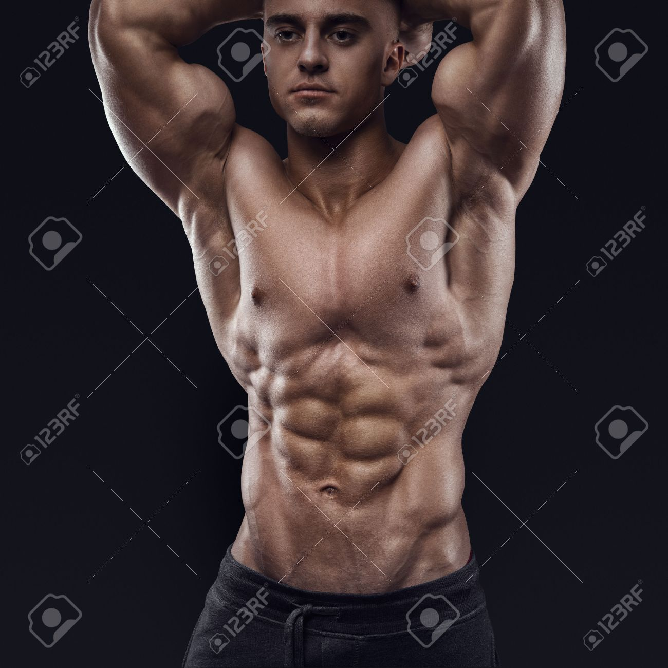 Sexy shirtless male model young bodybuilder posing over black background studio shot on black background
