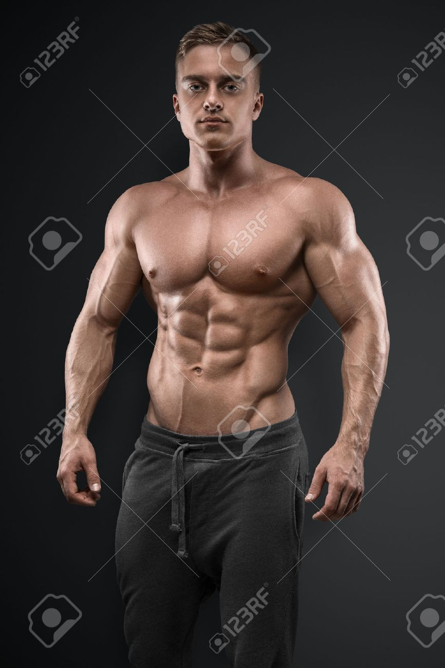 Handsome power athletic man posing on black background. Strong bodybuilder with six pack, perfect abs, shoulders, biceps, triceps and chest Standard-Bild - 44585833
