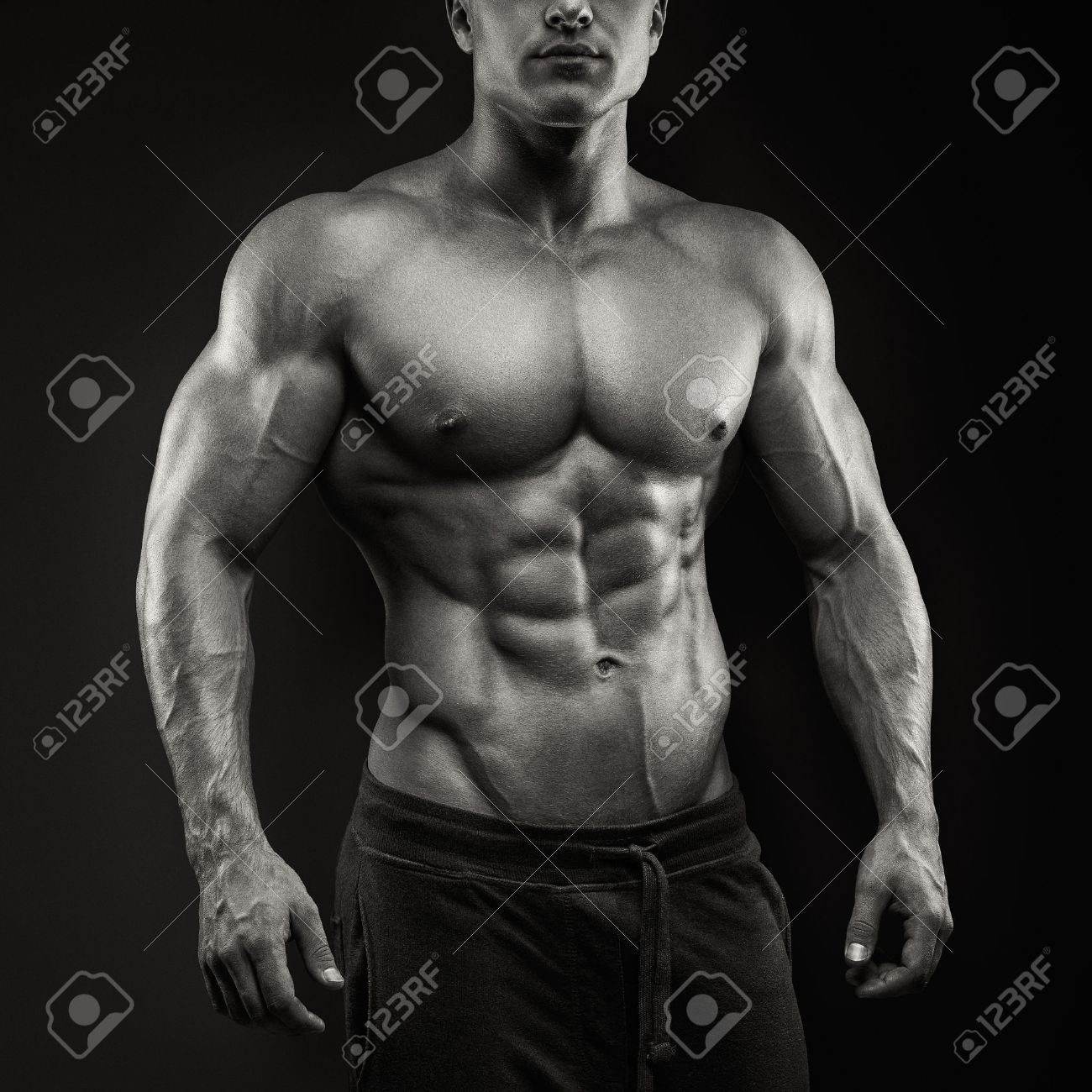 Handsome power athletic man posing on black background. Strong bodybuilder with six pack, perfect abs, shoulders, biceps, triceps and chest Standard-Bild - 44585914