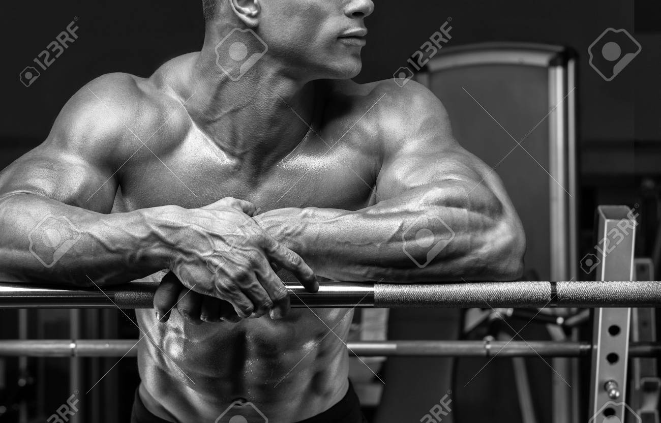 Close up of handsome bodybuilder guy prepare to do exercises with barbell in a gym. Black and white photo. Standard-Bild - 52526430