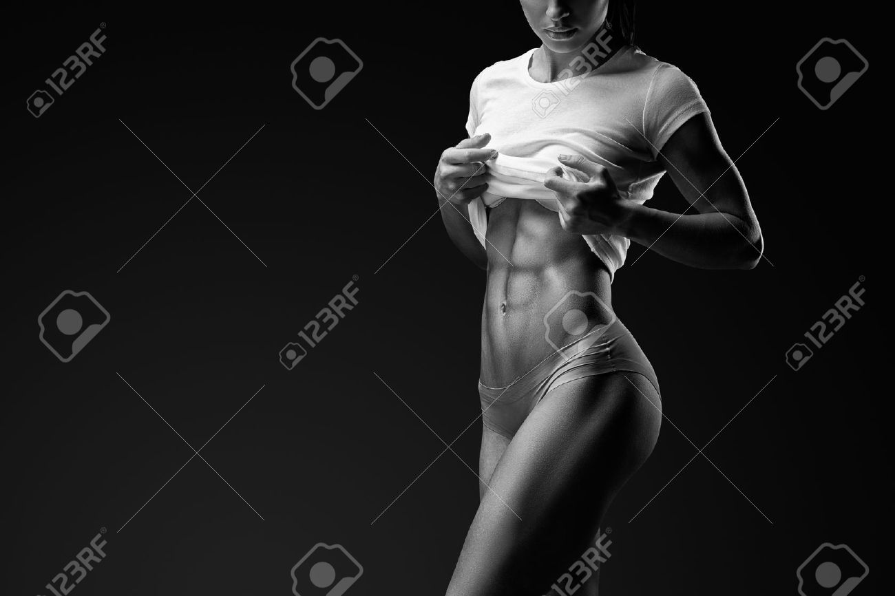 Black and white portrait of young woman with muscular body standing against black background. Image of fitness woman in sports clothing. Standard-Bild - 61824969