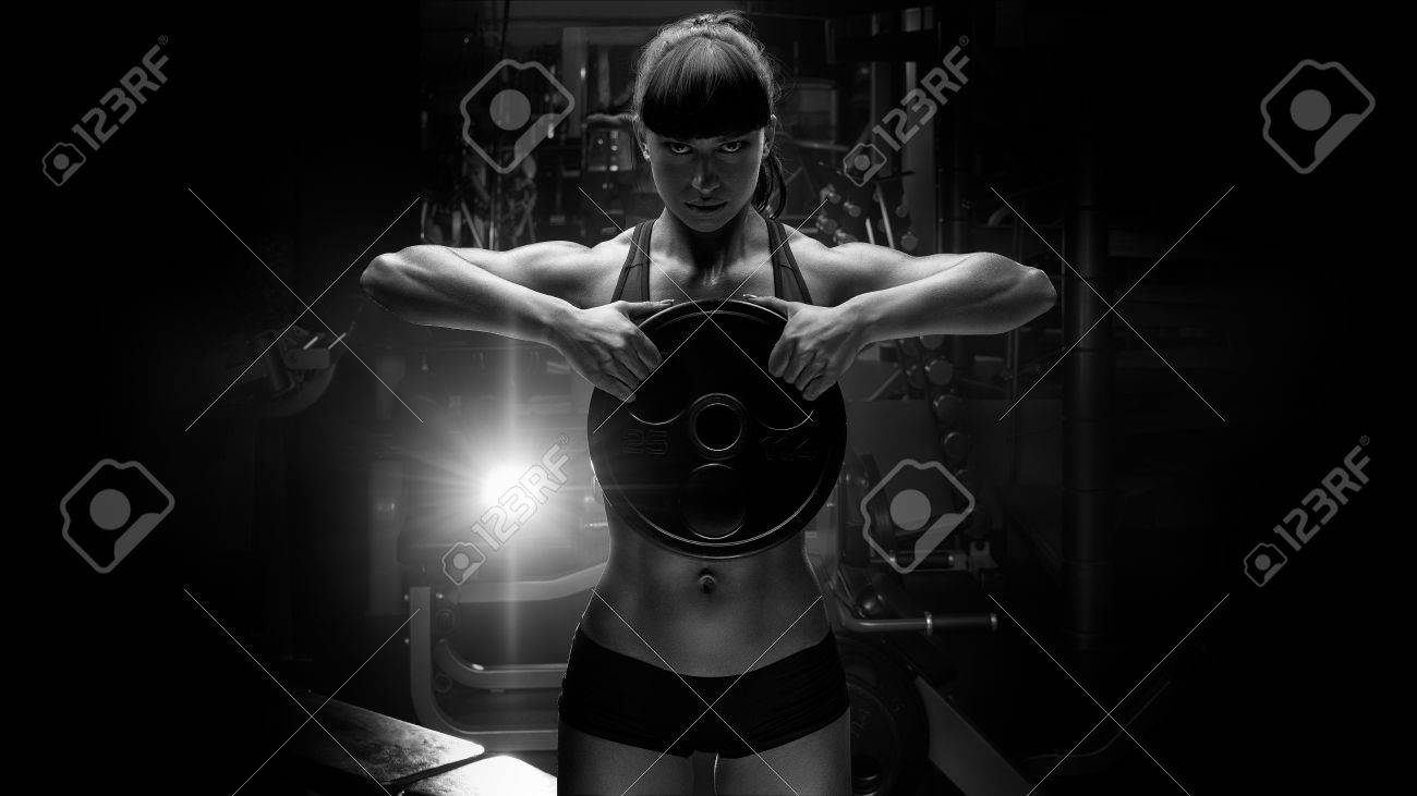 Black and white portrait of fit power athletic confident young woman crossfit trainer doing exercises with