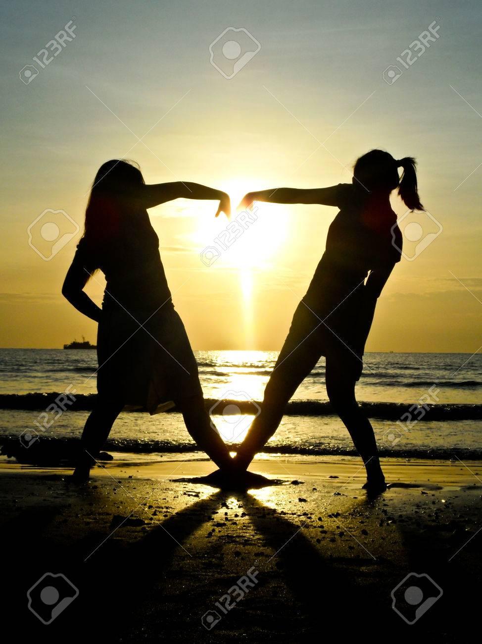 Due Ragazze Che Fanno Il Cuore Con Il Mare E Lo Sfondo Sole Giù