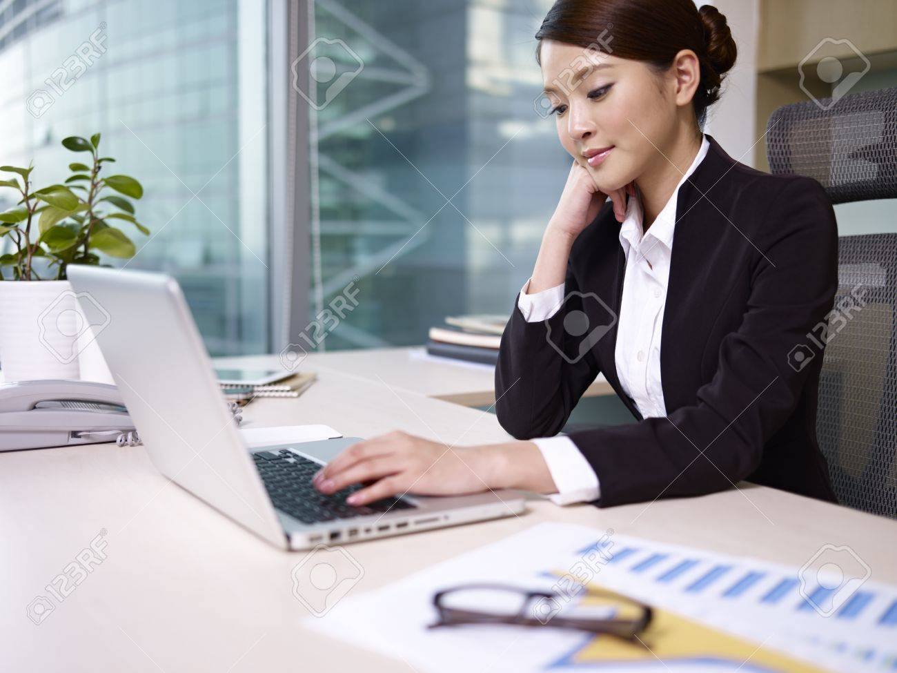 asian businesswoman looking at laptop computer in office Stock Photo - 18117917