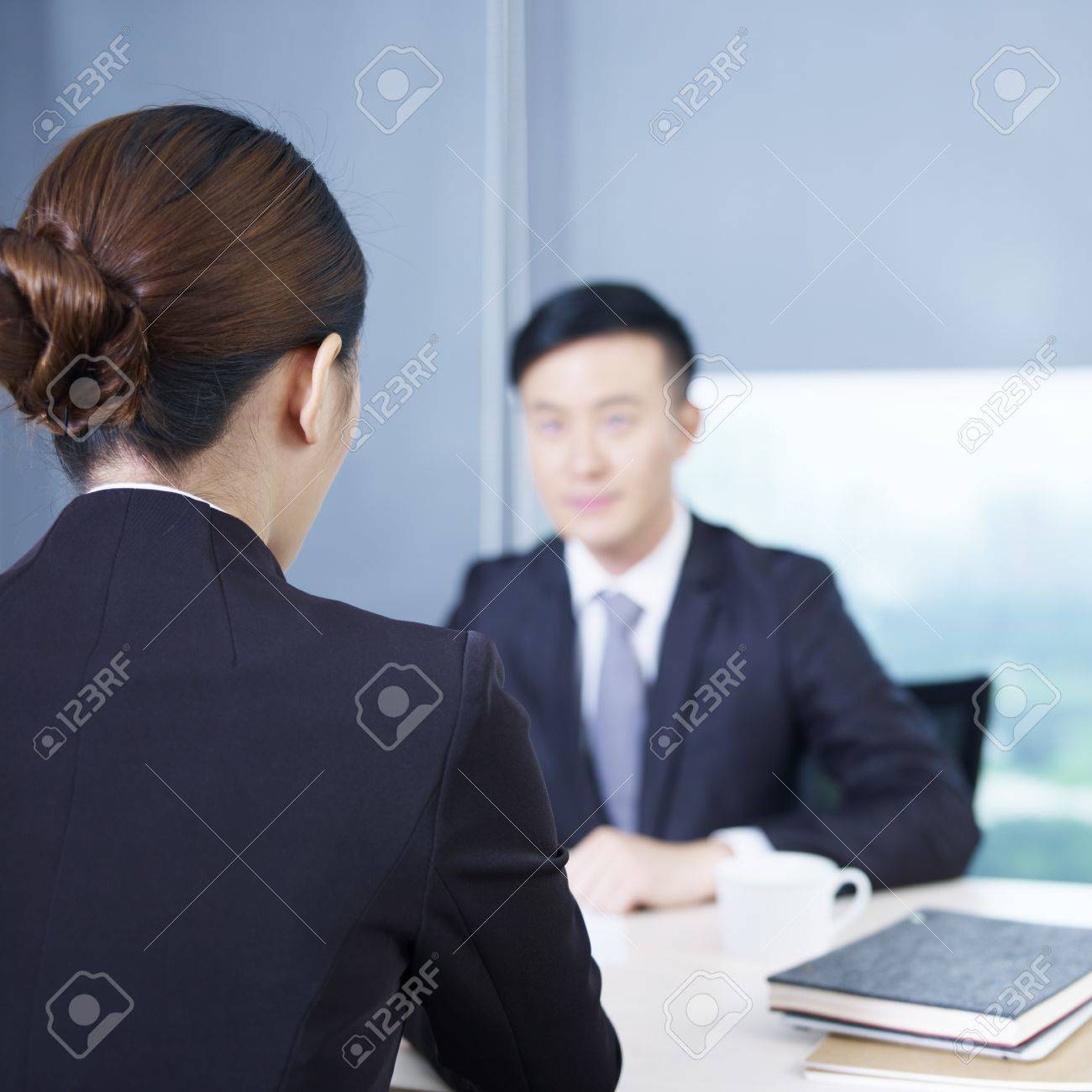 rear view of an interviewer talking to a nervous interviewee stock stock photo rear view of an interviewer talking to a nervous interviewee