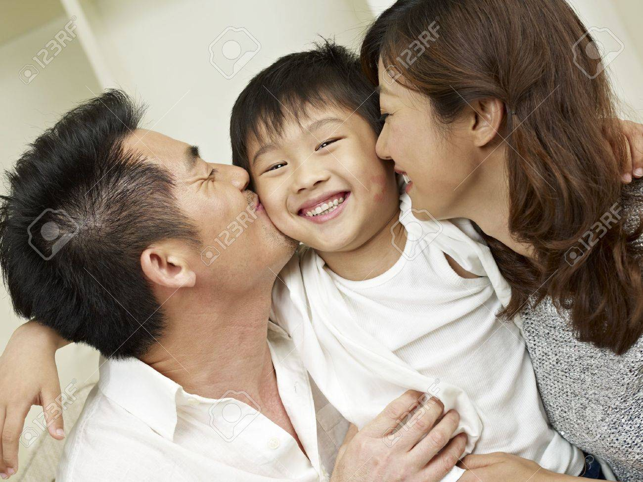 little boy kissed by mother and father Stock Photo - 20044043