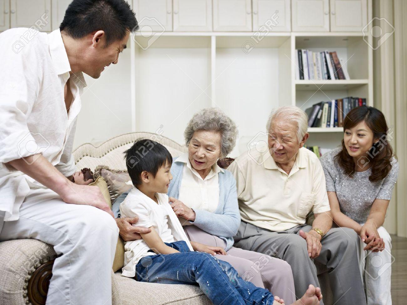Three-generation Asian Family Talking In Living Room Stock Photo ...