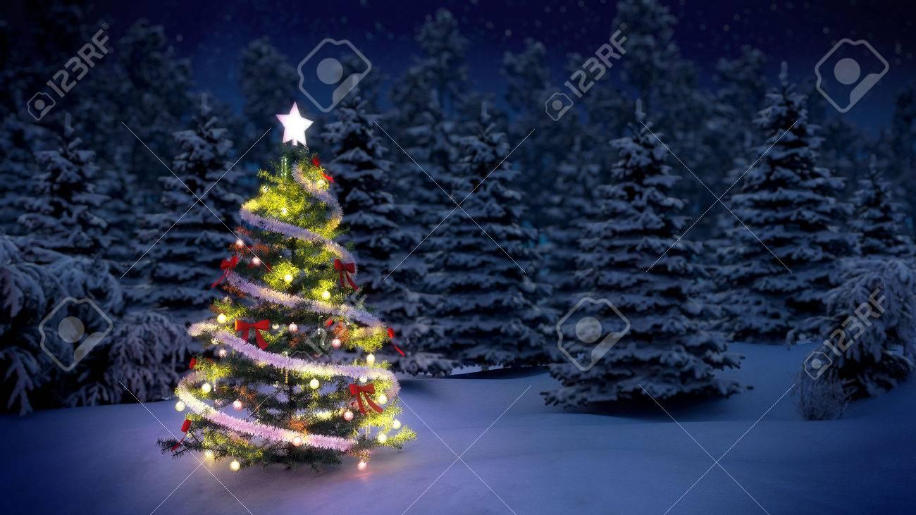 Shiny Christmas Tree Before Snow Covered Trees At Night Stock Photo