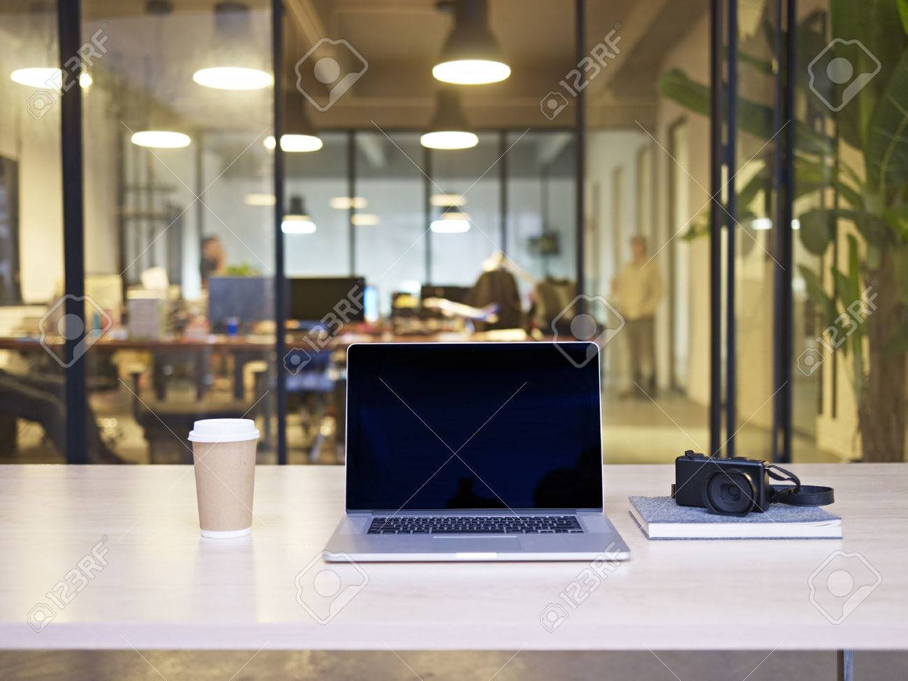 small business office laptop computer camera coffee on top of a table in business office modern