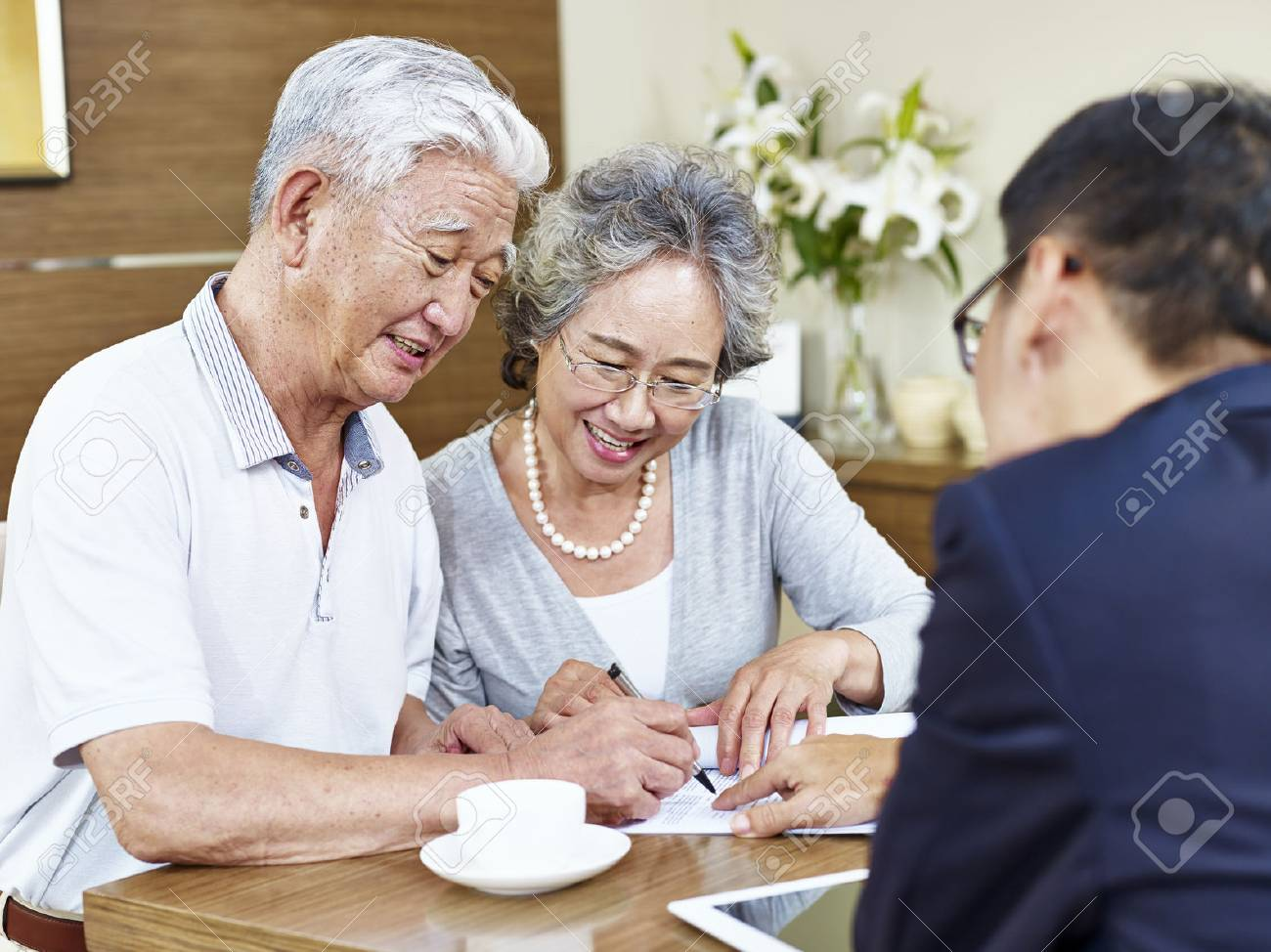 happy senior asian couple signing a contract agreement in front a salesperson. - 67953987