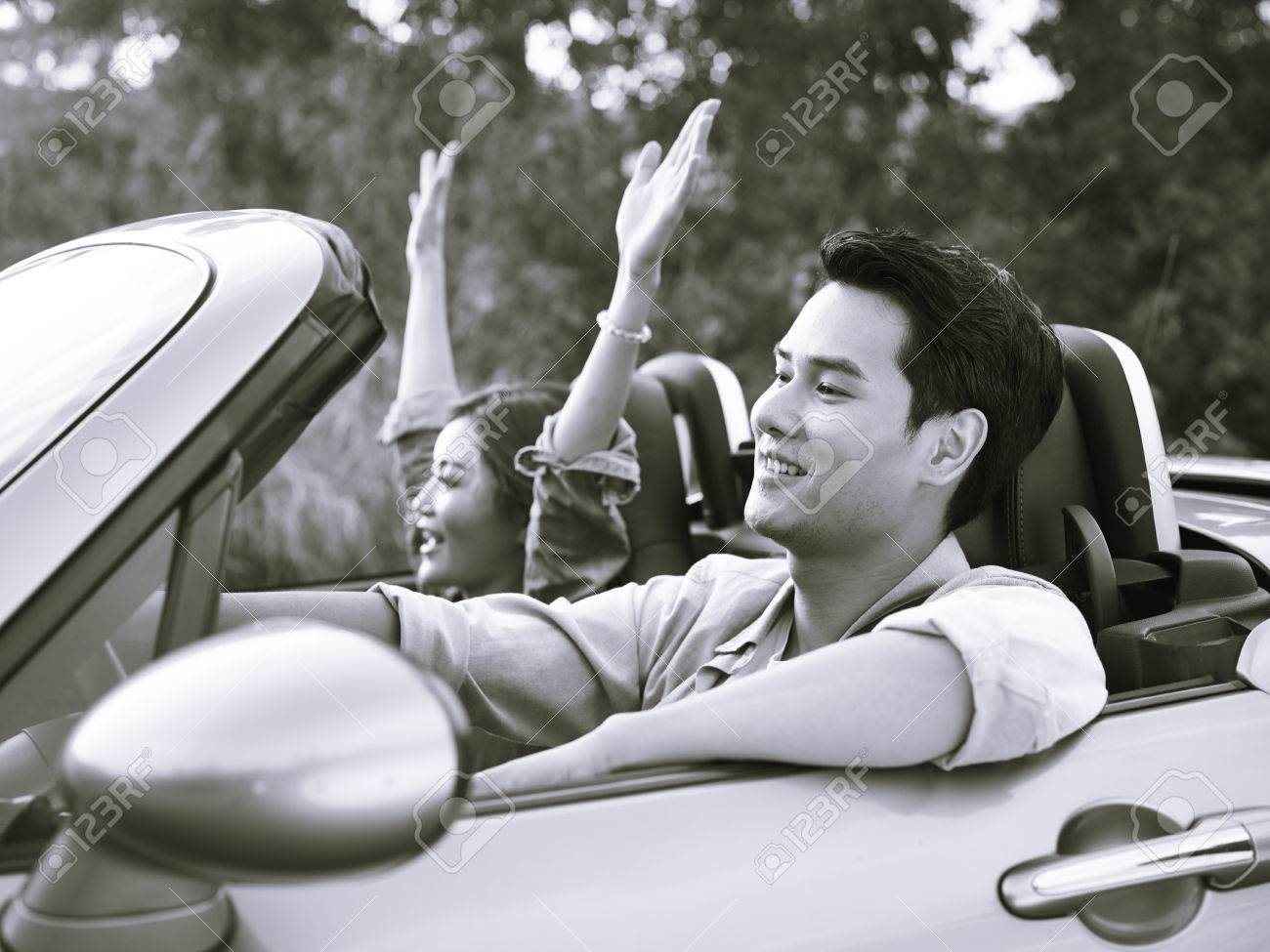 Young Asian Couple Riding In A Convertible Sport Car Enjoying The Cool  Breeze At Sunset,