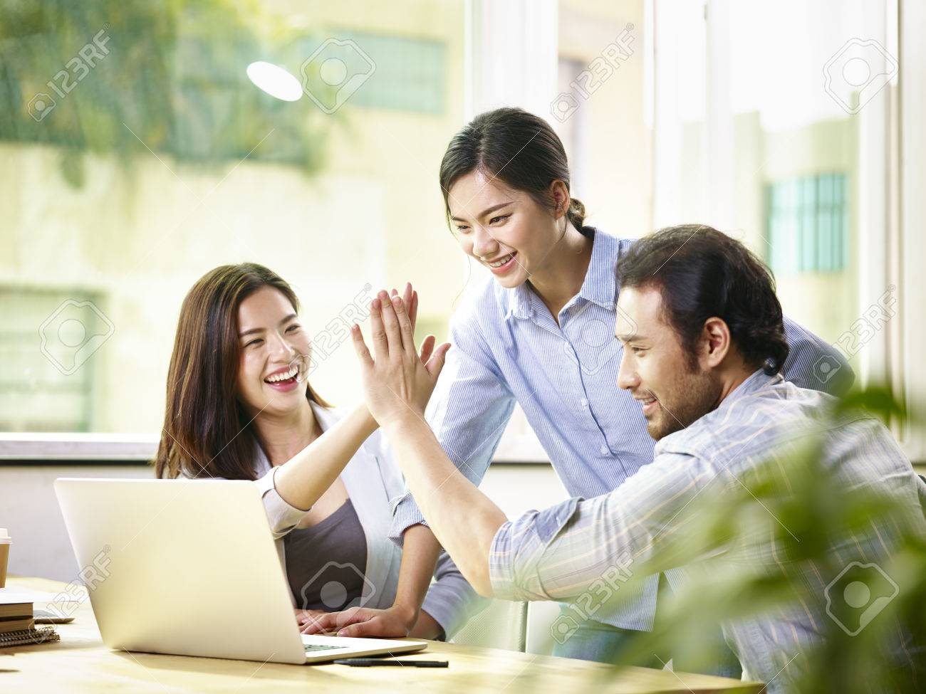 young asian business person giving coworker high five in office celebrating achievement and success. - 81035336