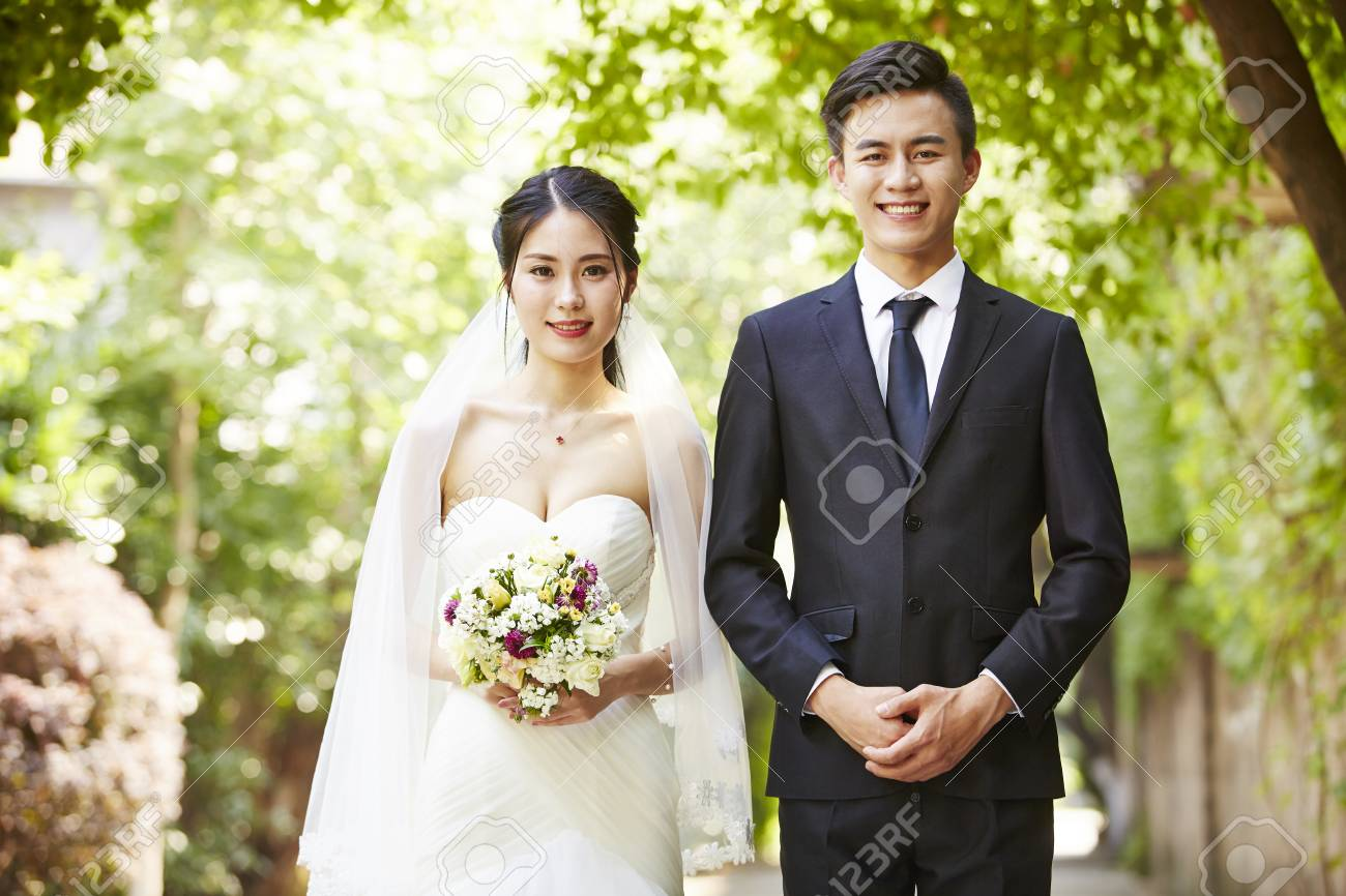 outdoor portrait of asian bride and groom looking at camera smiling. - 86053723
