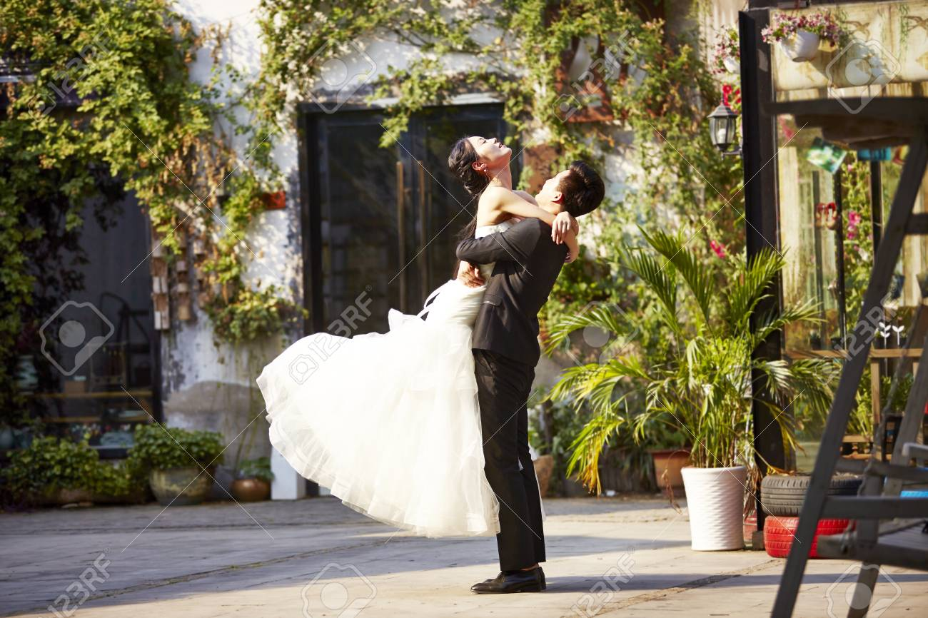 asian newly wed bride and groom celebrating marriage outside a building. - 86053724
