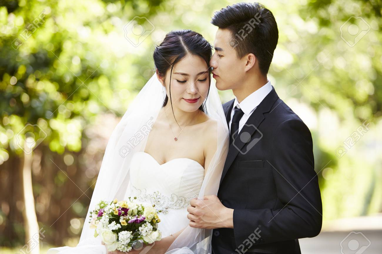 young asian groom kissing bride outdoors during wedding ceremony. - 86610110