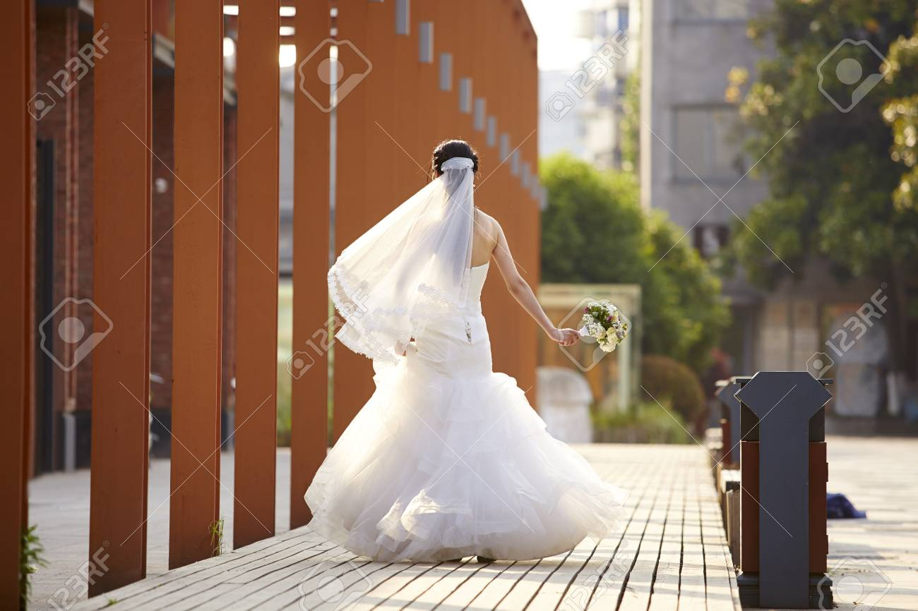 Asian Bride In White Wedding Dress Walking With A Bouquet, Rear ...